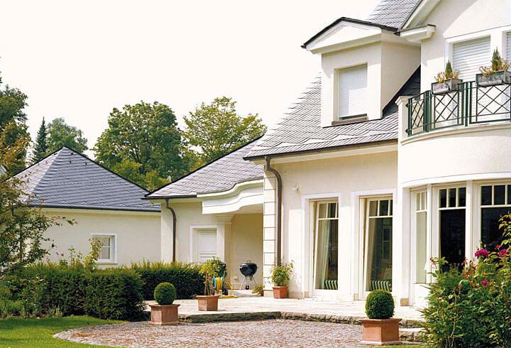 Delikatnie i elegancko prezentują się dwa pokryte łupkiem domy w stylizowanym na park ogrodzie. Pokrycie łupkowe sprawia wrażenie delikatnego, dyskretnego i spokojnego.