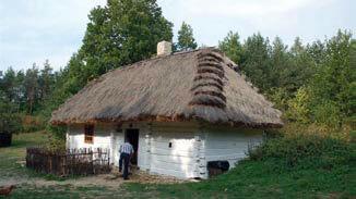 Biedna chata chłopska jednoizbowa z częścią dla zwierząt, z XIX w., pobielone ściany drewniane na zrąb, dach kopertowy pokryty gładko strzechą.