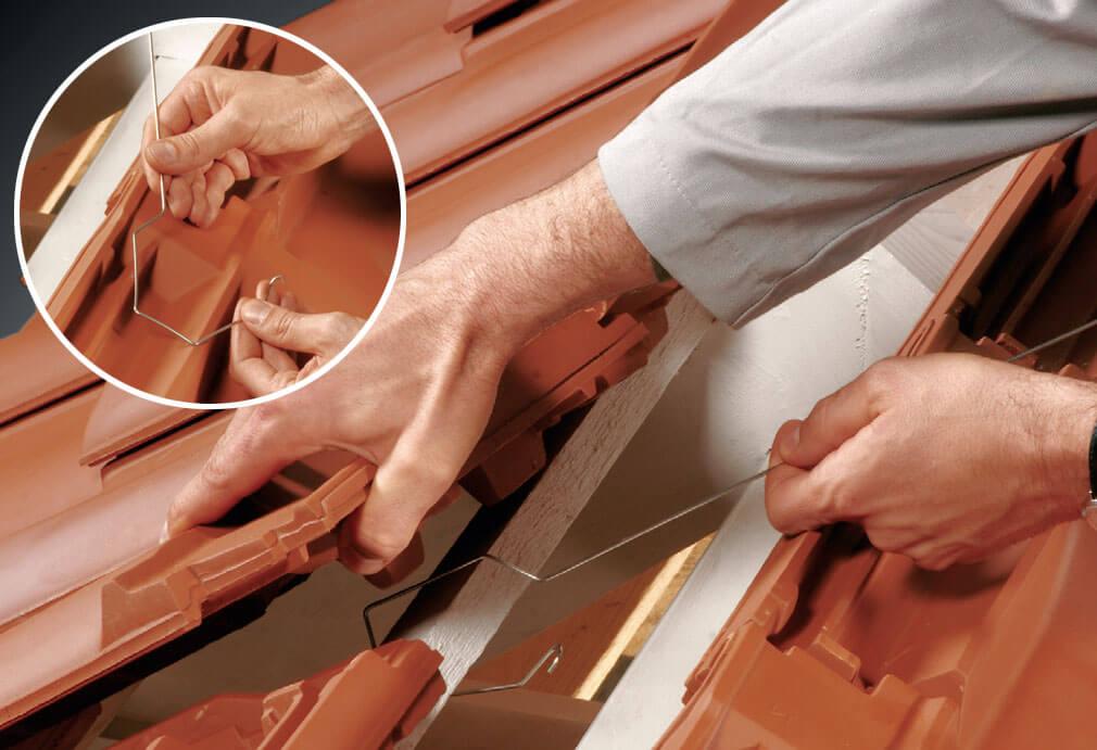 Fot. 2. Druty montażowe zaczepia się naprzemiennie do ostatniej łaty dachowej, raz po prawej, raz po lewej stronie, w odstępach wynoszących ok. 42 cm. Uniesienie dachówki kalenicowej wentylacyjnej ułatwia montaż.