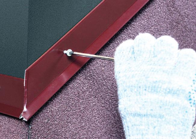 Montaż gontów. Listwa dociskowa ma zapewnić uszczelnienie papy na kominie.