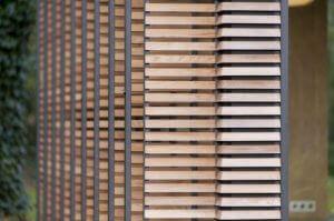 Drewniane żaluzje na jednej ze ścian można różnie ustawiać, wpuszczając więcej lub mniej słońca