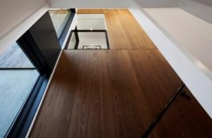 """Dom z """"miedzianego drewna"""" - Klatka schodowa nawiązuje do zewnętrznych okładzin z drewna modyfikowanego termicznie."""
