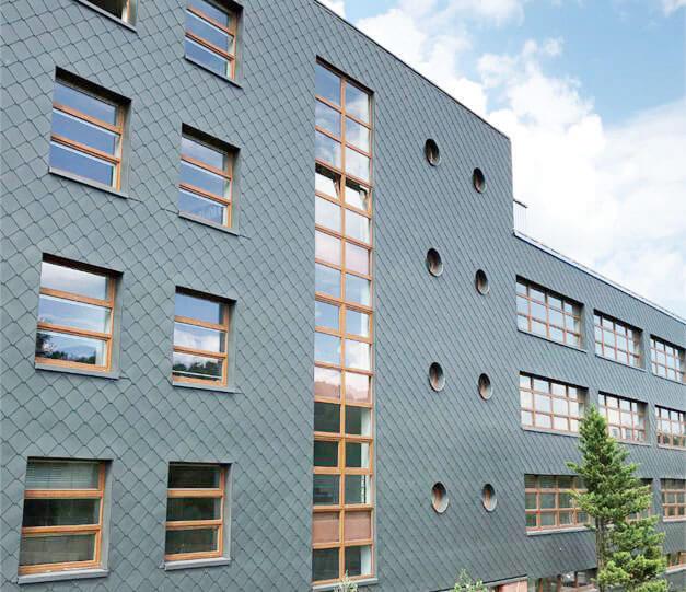 Fasada szkoły zawodowej w Libercu w Czechach to także inspirująca architektura. Wyróżniający się jako kluczowy element fasady grafitowe łuski MULTI-FORM w powierzchni RHEINZINK-prePATINA schiefergrau podkreślają nowoczesny wygląd budynku